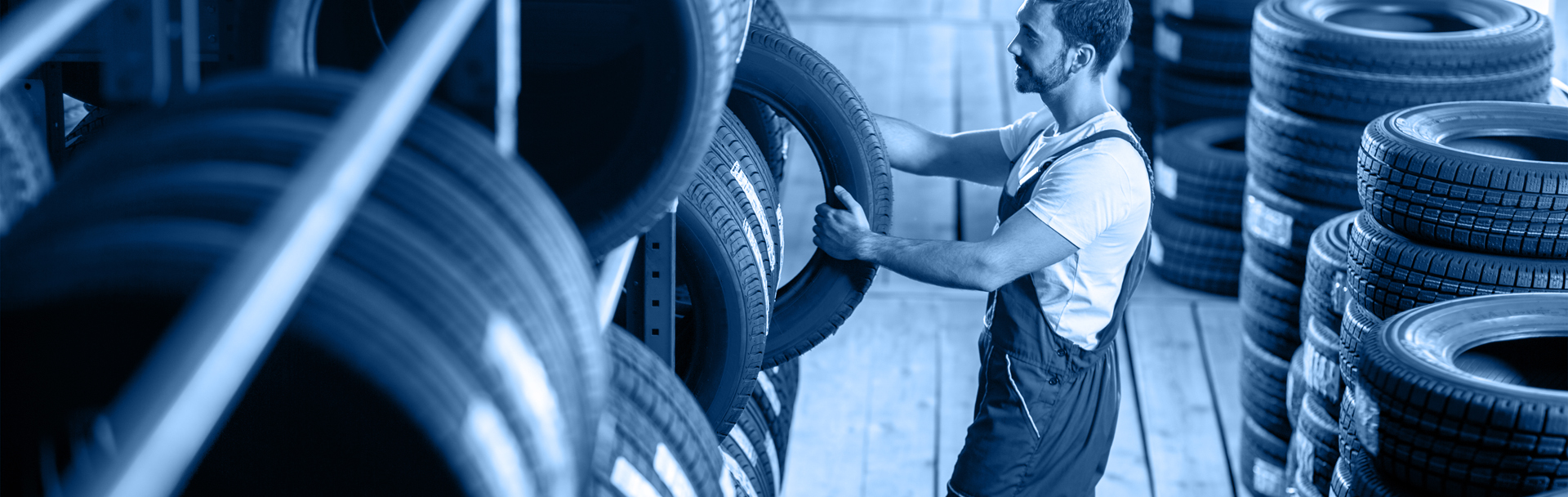 Mechanic choosing a tyre from stock - Tyres Dartford